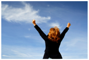 Image of a triumphant business-woman with her arms in the air