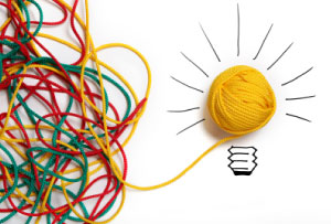 Photo of a confused mess of wool leading to a lightbulb, to symbolise career insight