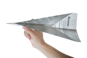 Picture of someone making a resume into a targeted paper airplane